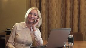 La muchacha hermosa llama por el teléfono móvil y habla feliz almacen de video