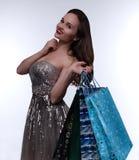La muchacha hermosa lleva a cabo paquetes de las compras Foto de archivo libre de regalías