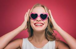 La muchacha hermosa lleva los vidrios con el borde rosado Ella está mirando para arriba y sonrisa La muchacha está llevando a cab Fotos de archivo
