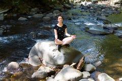 La muchacha hermosa medita sentarse en una piedra fotografía de archivo