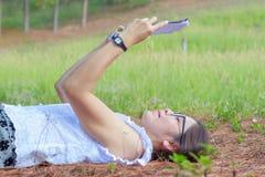 La muchacha hermosa miente en prado y lee el libro Fotos de archivo