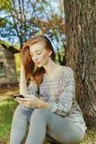 La muchacha hermosa mira en el teléfono Fotografía de archivo libre de regalías