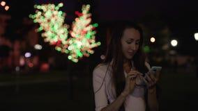 La muchacha hermosa mira noticias en el smartphone