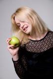 La muchacha hermosa mira para arriba con una sonrisa en una manzana verde Fotografía de archivo libre de regalías