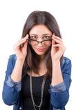 La muchacha hermosa mira sobre los vidrios Imagen de archivo