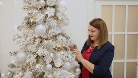 La muchacha hermosa misma adorna el árbol de navidad almacen de video