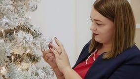 La muchacha hermosa misma adorna el árbol de navidad almacen de metraje de vídeo