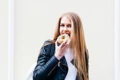 La muchacha hermosa muerde un buñuelo delicioso que camina en las calles de la ciudad europea Primavera caliente outdoor Cierre p Fotos de archivo libres de regalías
