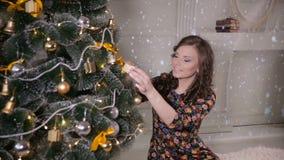La muchacha hermosa, mujer joven que adornaba el árbol de navidad, puso los juguetes del Año Nuevo y las bolas en el árbol de nav almacen de metraje de vídeo