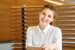La muchacha hermosa pasa tiempo con los artilugios en un café Fotos de archivo