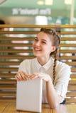 La muchacha hermosa pasa tiempo con los artilugios en un café Foto de archivo