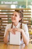 La muchacha hermosa pasa tiempo con los artilugios en un café Imagenes de archivo