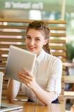 La muchacha hermosa pasa tiempo con los artilugios en un café Imagen de archivo libre de regalías