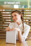 La muchacha hermosa pasa tiempo con los artilugios en un café Imagen de archivo