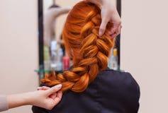 La muchacha hermosa, pelirroja con el pelo largo, peluquero teje una trenza francesa, en un salón de belleza foto de archivo libre de regalías
