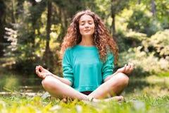 La muchacha hermosa practica yoga en el bosque de la mañana Imagen de archivo