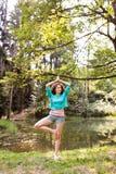 La muchacha hermosa practica yoga en el bosque de la mañana Imágenes de archivo libres de regalías