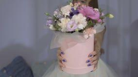 La muchacha hermosa presenta la caja festiva con el ramo de flores metrajes