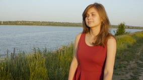 La muchacha hermosa que camina a lo largo del riverbank con las cañas en la puesta del sol, mujer linda camina en naturaleza en e almacen de video