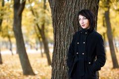 La muchacha hermosa que coloca el árbol cercano en el parque de la ciudad del otoño, amarillo se va en el fondo, temporada de oto Imagenes de archivo