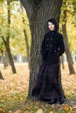 La muchacha hermosa que coloca el árbol cercano en el parque de la ciudad del otoño, amarillo se va en el fondo, temporada de oto Fotos de archivo libres de regalías