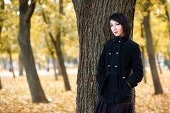 La muchacha hermosa que coloca el árbol cercano en el parque de la ciudad del otoño, amarillo se va en el fondo, temporada de oto Foto de archivo