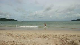 La muchacha hermosa que disfruta de días de fiesta de la playa del verano entra en el mar Vacaciones del viaje de la mujer feliz  metrajes