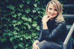 La muchacha hermosa que el blonde se sienta en las escaleras de un metal Imágenes de archivo libres de regalías