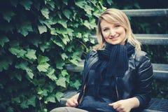 La muchacha hermosa que el blonde se sienta en las escaleras de un metal Fotos de archivo