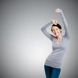 La muchacha hermosa que gesticula los puños triunfales es feliz Foto de archivo