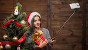 La muchacha hermosa que hace selfies acerca al árbol del Año Nuevo Imagen de archivo