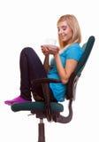 La muchacha hermosa que se relaja en silla sostiene una taza de té o de café. Imagenes de archivo