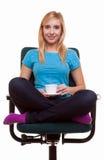 La muchacha hermosa que se relaja en silla sostiene una taza de té o de café. Imagen de archivo libre de regalías