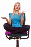 La muchacha hermosa que se relaja en silla sostiene una taza de té o de café. Fotos de archivo libres de regalías
