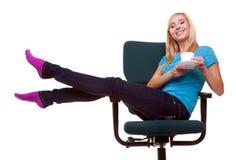 La muchacha hermosa que se relaja en silla sostiene una taza de té o de café. Fotografía de archivo libre de regalías