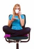 La muchacha hermosa que se relaja en silla sostiene una taza de té o de café. Imágenes de archivo libres de regalías