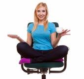 La muchacha hermosa que se relaja en silla sostiene una taza de té o de café. Fotografía de archivo