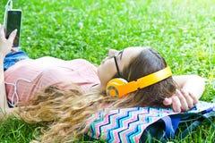La muchacha hermosa que se relaja y escucha música Fotografía de archivo libre de regalías