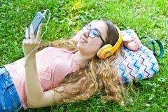 La muchacha hermosa que se relaja y escucha música en los auriculares en th Fotografía de archivo libre de regalías