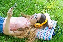 La muchacha hermosa que se relaja y escucha música en los auriculares en th Fotos de archivo