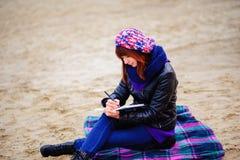 La muchacha hermosa que se sienta en la playa y tiene expedientes en un noteboo Fotografía de archivo