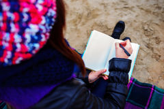 La muchacha hermosa que se sienta en la playa y tiene expedientes en un noteboo Imagen de archivo