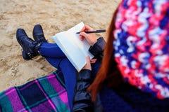 La muchacha hermosa que se sienta en la playa y tiene expedientes en un noteboo Foto de archivo libre de regalías