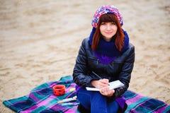La muchacha hermosa que se sienta en la playa y tiene expedientes en un noteboo Fotos de archivo libres de regalías