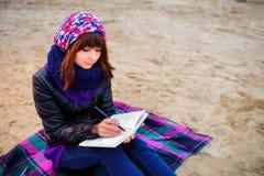 La muchacha hermosa que se sienta en la playa y tiene expedientes en un noteboo Imagenes de archivo