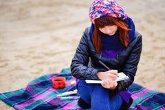 La muchacha hermosa que se sienta en la playa y tiene expedientes en un noteboo Foto de archivo
