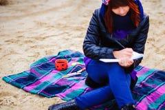 La muchacha hermosa que se sienta en la playa y tiene expedientes en un noteboo Imagen de archivo libre de regalías