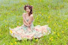 La muchacha hermosa que se sienta en la tierra cerca de la pared en vaqueros y una blusa blanca, su pelo desarrolla el viento Fotografía de archivo libre de regalías