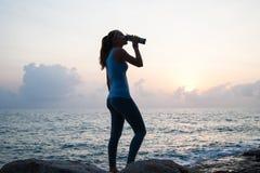 La muchacha hermosa que se sienta en piedras y que mira en una distancia, la muchacha en la puesta del sol para meditar en el sil Imagen de archivo