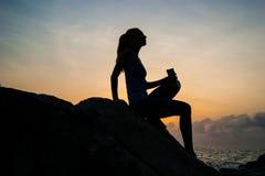 La muchacha hermosa que se sienta en piedras y que mira en una distancia, la muchacha en la puesta del sol para meditar en el sil Fotos de archivo libres de regalías